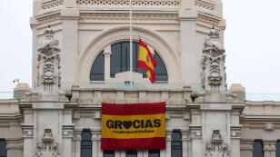 La bandera española ondea a media asta sobre un mensaje de agradecimiento a la gente por quedarte en casa en el Ayuntamiento de Madrid.