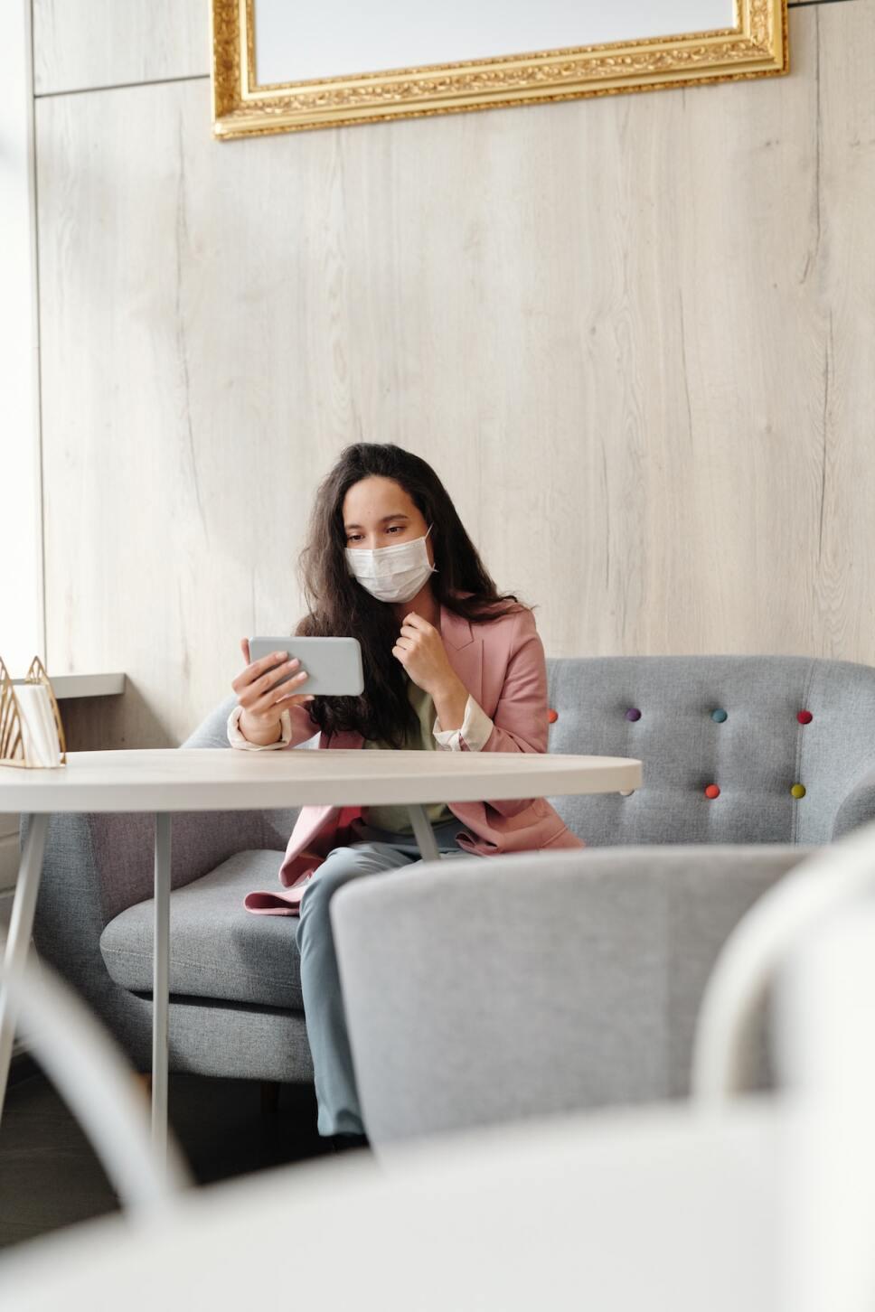 mujer vacunada en celular con cubrebocas