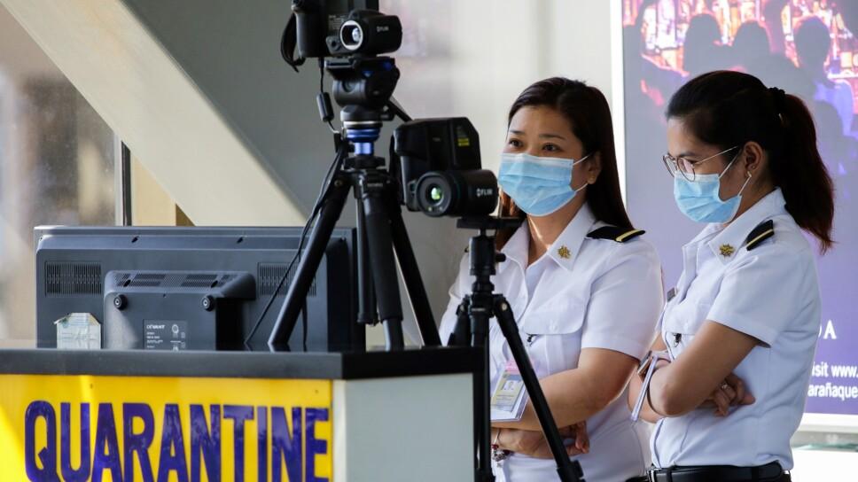 Funcionarios monitorean con un escáner térmico a los pasajeros que llegan al Aeropuerto Internacional Ninoy Aquino, en Pasay, Manila, Filipinas.
