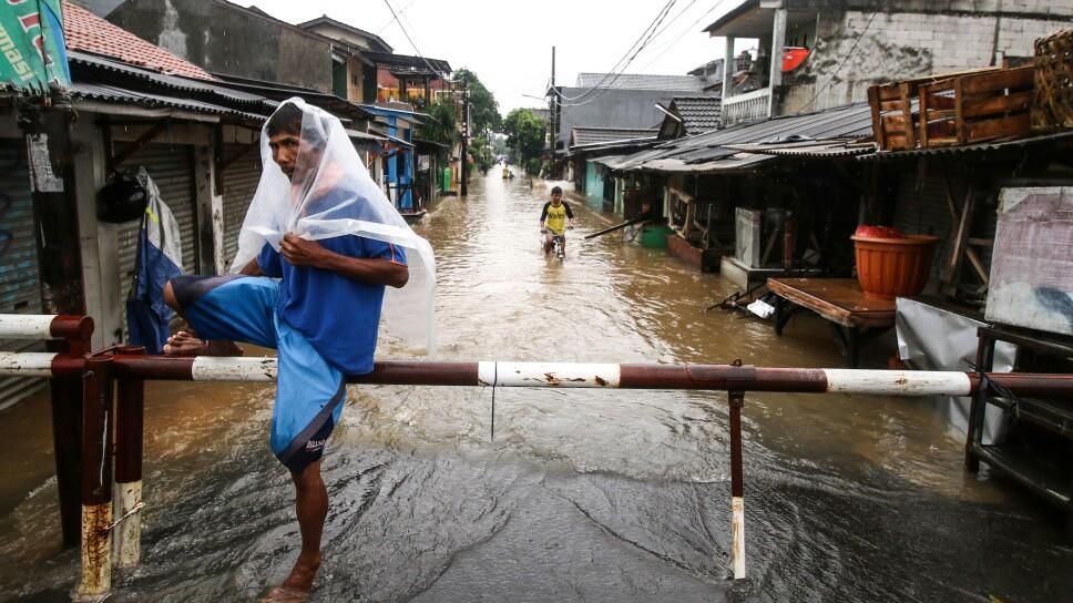 Un hombre con una lámina de plástico viaja por una calle inundada en la residencia Pondok Maharta, en el sur de Tangerang, cerca de Yakarta, Indonesia, el 25 de febrero de 2020 en esta foto tomada por Antara Foto