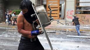 Un manifestante se protege con un lavaplatos durante una protesta contra el gobierno en Santiago de Chile
