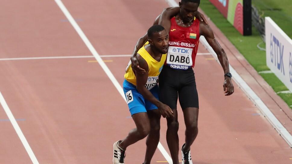 Jonathan Busby de Aruba es ayudado a llegar a la meta por Braima Suncar Dabo de Guinea-Bissau en la prueba de 5.000 metros en el Mundial de Atletismo en Qatar.