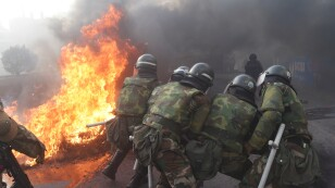 Members of the military police try to destroy a barricade in Sacaba, on the outskirts of Cochabamba