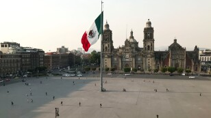 People walk near the national flag and the Metropolitan Cathedral on a Zocalo Square partially empty as the coronavirus disease (COVID-19) outbreak continues, in Mexico City