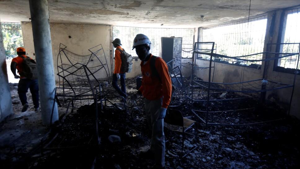 Trabajadores de protección civil supervisan una habitación en un orfanato que sufrió un incendio mortal en Puerto Príncipe, Haití.