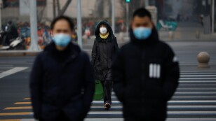 People wearing masks walk across a street as the country is hit by an outbreak of the new coronavirus, in Beijing