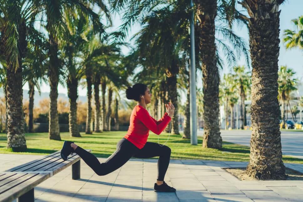 mujer haciendo un desplante en una banca ejercicio al aire libre