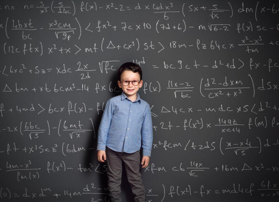 Little child in front of huge blackboard