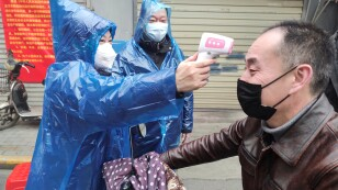Worker takes body temperature measurement of a man at the entrance to a residential compound following an outbreak of the new coronavirus in Wuhan