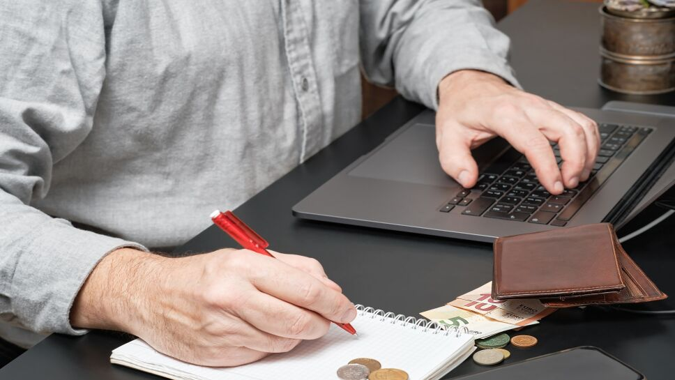 Close-up of a businessman or accountant holding pen working at desk using a laptop to calculate financial report or tax payments. Business concept of accounting, paying taxes, calculating finances