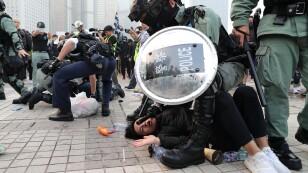 La policía arresta a un manifestante después de que una bandera china fuera retirada del asta de una bandera en un acto de apoyo a los derechos humanos de los uigures de Xinjiang en Hong Kong