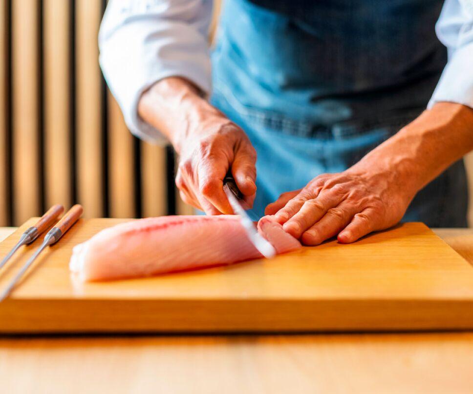 chef cortando pescado para comida japonesa